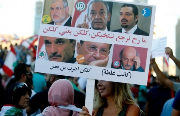 "Protesters holding a banner  that  shows the pics of the top  Lebanese politicians  that reads . ""We won't re-elect you . we mean all of you . You are all bad .. we made a mistake""."
