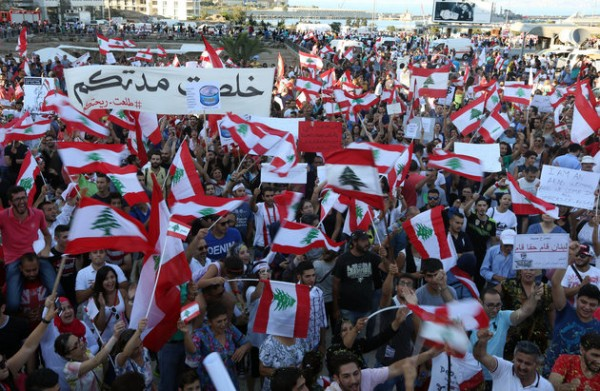 "Lebanese anti-government protesters wave Lebanese flags and and a  placard that tells politicians  "" your time is up"" during a demonstration in Martyrs' Square, downtown Beirut, Lebanon, Saturday, Aug. 29, 2015. Thousands of people staged the largest of the demonstrations that began last week over garbage piling up in the streets of Beirut following the closure of a main landfill. The government's failure to resolve the crisis has evolved into wider protests against a political class that has dominated Lebanon since the end of the country's civil war in 1990 and a government that has failed to provide even basic services to the people. (AP Photo/Bilal Hussein)"