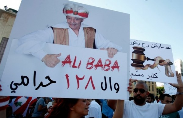 Protesters holding a banner that shows Lebanon parliament  Speaker  Nabih Berri and that reads  Ali Baba and the 128 thieves . The Lebanese parliament has 128 members.  Beirut Aug 29, 2015