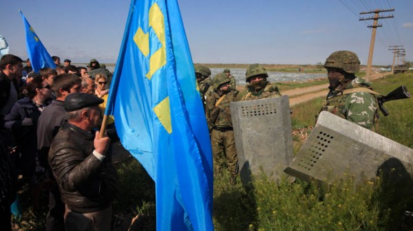 Russian troops blocking Crimean Tatars from crossing a checkpoint connecting Crimea and the Kherson region.