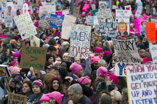 Women with bright pink hats and signs begin to gather early and are set to make their voices heard on the first full day of Donald Trump's presidency, January 21, 2017 in Washington. AP Photo/Jose Luis Magana