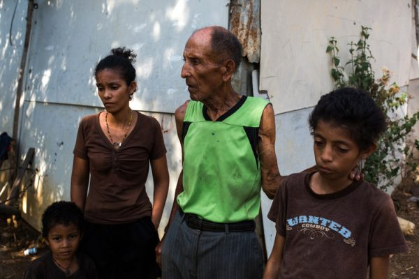 Cesar Palma, 75 years old, receives a monthly pension now worth about $10 a month. He goes hungry some days trying to feed his grown daughter and her three children, including Germain, right. PHOTO: WIL RIERA FOR THE WALL STREET JOURNAL