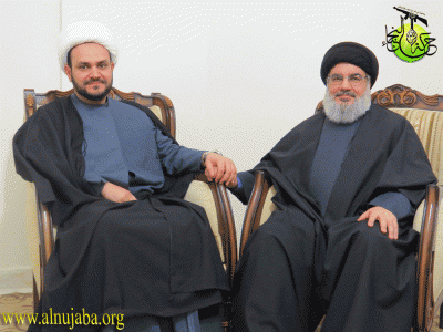 Akram Kaabi  Kaabi, the Secretary General of the Harakat Hezbollah  Nujaba, holds hands with Hassan Nasrallah, the leader of Lebanon's Hezbollah. Image from the League of the Righteous's website.