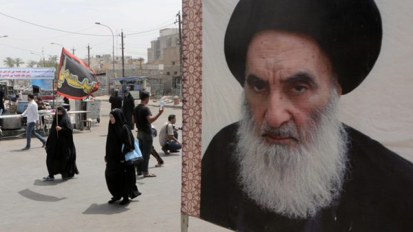Shiite pilgrims make their way to the shrine of Imam Moussa al-Kadhim as passing by a poster of Shiite spiritual leader Grand Ayatollah Ali al-Sistani, right, in Baghdad, Iraq, Thursday, May 22, 2014. Shiite pilgrims are expected to converge on the shrine in northern Baghdad during their annual march to commemorate the eighth-century death of Imam Moussa al-Kadhim, a key Shiite saint. (AP Photo/Khalid Mohammed)