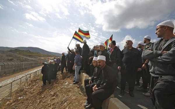 Druze men in the Israeli occupied Golan Heights congregate near the Syrian border, waving their community's flag,