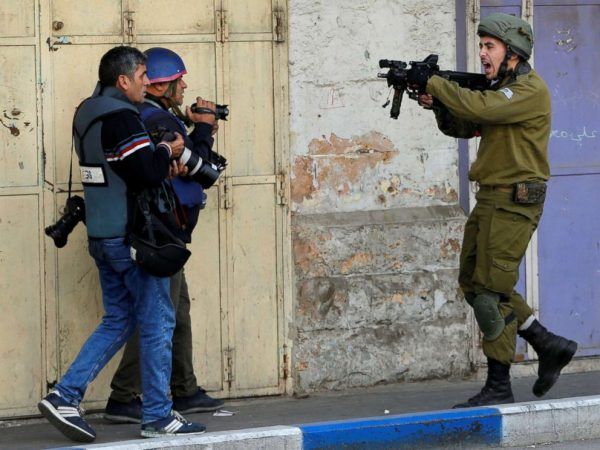 An Israeli soldier shouts as he aims his weapon during clashes with Palestinian demonstrators at a protest against President Donald Trump's decision to recognize Jerusalem as the capital of Israel, in the West Bank city of Hebron, Dec. 15, 2017.