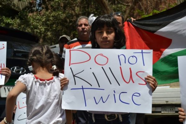 A Palestinian youth is   protesting against the UNRWA funding cuts .The  banner   reads do not kill us twice