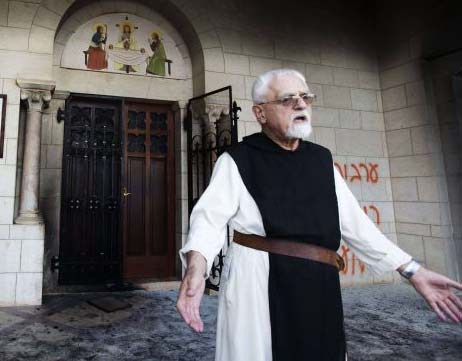 A Catholic monk stands in a doorway of the Latrun Trappist Monastery where Israeli police say Jewish vandals spray-painted anti-Christian and pro-settler graffiti and set the monastery's door on fire, in Latrun, between Jerusalem and Tel Aviv, Israel. (AP/Oded Balilt)