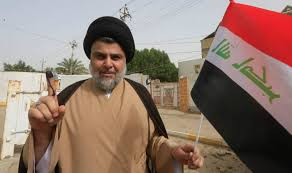 Iraqi  leader Muqtada al-Sadr (C) shows his ink-stained index finger and holds a national flag while surrounded by people outside a polling station in the central holy city of Najaf, Iraq, May 12, 2018.