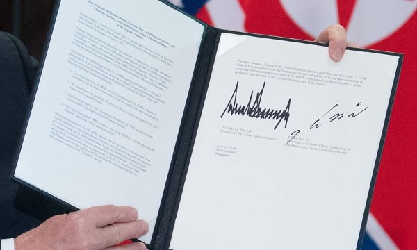 Donald Trump holds up the document signed by him and Kim Jong-un at a ceremony during their historic summit in Singapore. Photograph: Saul Loeb/AFP/Getty Images