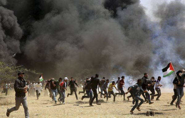 Palestinian protesters run to cover from teargas fired by Israeli soldiers during clashes with Israeli troops along Gaza's border with Israel, east of Khan Younis, Gaza Strip, Friday, April 6, 2018. Palestinians torched piles of tires near Gaza's border with Israel on Friday, sending huge plumes of black smoke into the air and drawing Israeli fire that killed one man in the second large protest in the volatile area in a week. (AP Photo/Adel Hana)