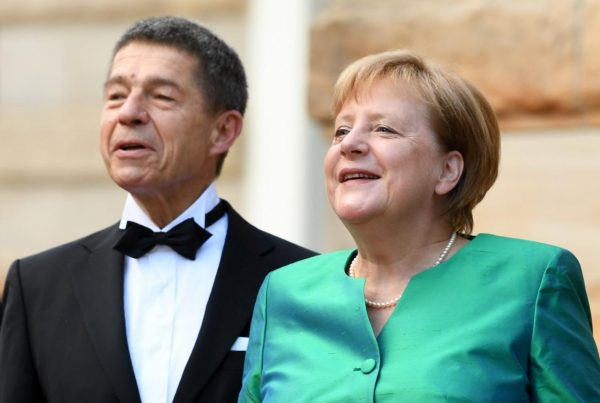 FILE PHOTO: German Chancellor Angela Merkel reacts next to her husband Joachim Sauer as they arrive for the opening of the Bayreuth Wagner Festival at The Richard Wagner Festival Hall on the Green Hill (Gruener Huegel) in Bayreuth, Germany, July 25, 2018. REUTERS/Andreas Gebert/File Photo