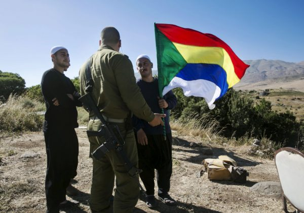 A member of the Druze community holds a Druze flag as he speaks to an Israeli soldier near the border fence between Syria and the Golan Heights, near Majdal Shams June 18, 2015. Gathered at a hilltop in the Golan Heights, a group of Druze sheikhs look through binoculars at the Syrian village of Hade. (photo credit: BAZ RATNER/REUTERS)