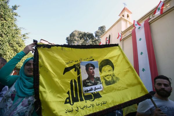 People carry a Hezbollah flag with a picture of newly elected  Lebanese President Michel Aoun stuck on it, in the Haret Hreik area, southern suburbs of Beirut, Lebanon October 31, 2016.