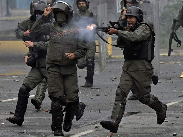 A member of the national guard fires hit shotgun at opposition demonstrators during clashes in Caracas last year (CARLOS BECERRA/AFP/Getty Images)