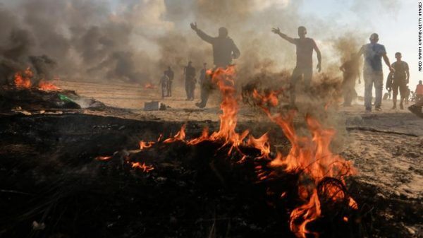 """Palestinian demonstrators burn tyres to protect themselves from Israeli forces' snipers during the """"Great March of Return"""" on the Gaza-Israel border in Rafah, Gaza on October 12, 2018.  (Photo by Abed Rahim Khatib/Anadolu Agency/Getty Images)"""