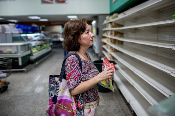 Fabiola Zerpa inspects empty bread shelves in the supermarket, grabbing a package of tortillas to purchase.
