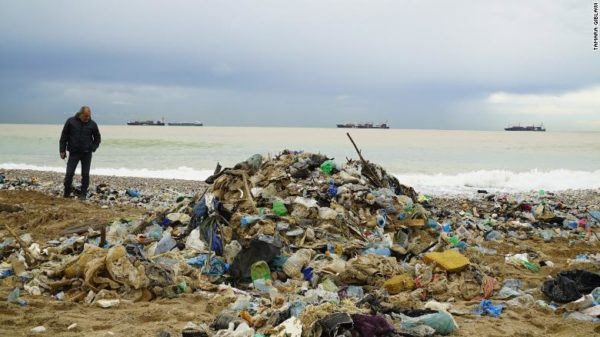 A garbage collector overses a clean-up one of north Beirut's trash-infested beaches.