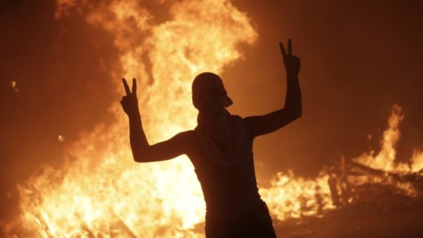 An anti-government protester makes victory signs in front a fire set by protesters to block a road during a demonstration in Beirut, Lebanon.CREDIT:AP