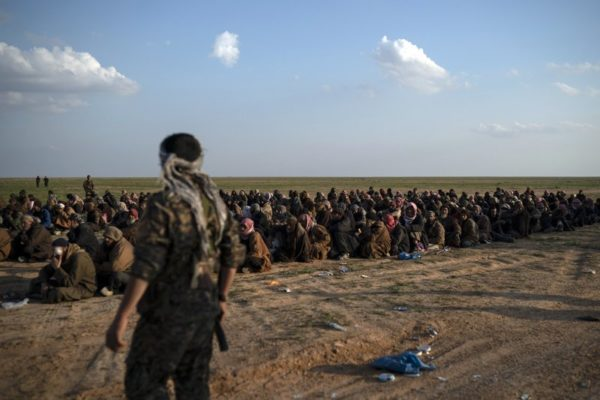 """FILE - In this Feb. 22, 2019 file photo, U.S.-backed Syrian Democratic Forces (SDF) fighters stand guard next to men waiting to be screened after being evacuated out of the last territory held by Islamic State group militants, near Baghouz, eastern Syria. The IS erupted from the chaos of Syria and Iraq's conflicts and swiftly did what no Islamic militant group had done before, conquering a giant stretch of territory and declaring itself a """"caliphate."""" U.S. officials said late Saturday, Oct. 26, 2019 that their shadowy leader Abu Bakr al-Baghdadi was the target of an American raid in Syria and may have died in an explosion. (AP Photo/Felipe Dana, File)"""