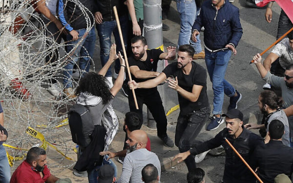 Anti-government protesters, left were attacked by Hezbollah supporters, right, during a protest near the government palace, in downtown Beirut, Lebanon, Friday, Oct. 25, 2019. (AP Photo/Hussein Malla)