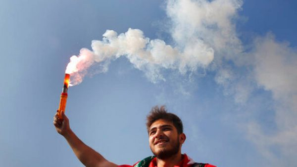 A student protester holds a smoke flare during a protest against the government in front of the education ministry in Beirut, Lebanon, Friday, Nov. 8, 2019. Lebanese protesters are rallying outside state institutions and ministries to keep up the pressure on officials to form a new government to deal with the country's economic crisis. HUSSEIN MALLA AP PHOTO